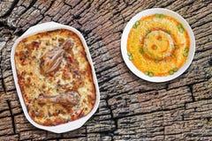 烤箱被烘烤的菜炖煮的食物用鸡肉和碗老树桩被风化的破裂的顶面上的被装饰的俄国沙拉集合 免版税库存照片