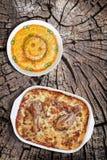 烤箱被烘烤的菜炖煮的食物用鸡肉和碗老树桩被风化的破裂的顶面上的被装饰的俄国沙拉集合 库存照片