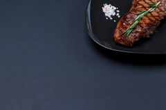 烤纽约牛排用迷迭香和桃红色himalanian盐o 免版税库存图片
