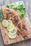 烤罗非鱼用在木板的草本 免版税库存照片