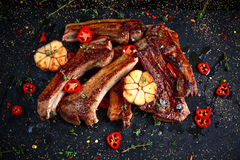 烤羊羔炸肉排肋骨用大蒜和草本在石背景 免版税库存图片