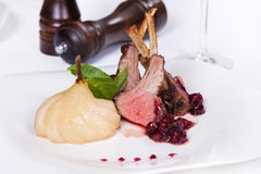 烤羊羔肋骨用调味汁、蓬蒿和梨 在白色背景的热的肉盘 库存照片