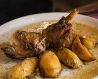 烤羊羔腿用在人板材的土豆 免版税图库摄影