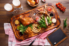 烤肉和不同的香肠服务与菜装饰 免版税库存照片