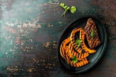 烤肉和南瓜在黑色的盘子 秋天菜单 顶视图 库存图片