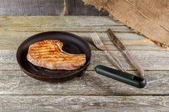 烤肉和菜在土气木桌上 美味调味汁和盐服务用在一土气木的烤牛排 免版税库存照片