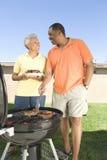 烤肉在草坪的愉快的夫妇 免版税图库摄影