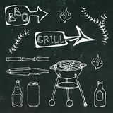 烤肉工具:BBQ叉子,钳子,格栅用肉,火,啤酒瓶,能,番茄酱,草本 在一个黑黑板上 库存照片