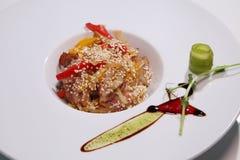 烤肉沙拉与菜和红辣椒,在一块白色板材的芝麻籽的 免版税库存图片