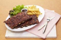 烤肉猪排服务与法语油煎的和沙拉 库存照片