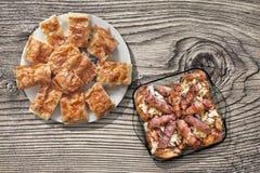 烤肉糕在玻璃烤盘的烟肉和鸡大腿滚动的Cevapcici用Gibanica被设置的乳酪饼在老木头 库存照片