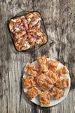 烤肉糕在玻璃烤盘的烟肉和鸡大腿滚动的Cevapcici用Gibanica被设置的乳酪饼在老木头 免版税库存照片