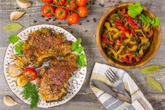 烤肉,蕃茄,胡椒,葱切了在一个白色盘切板的菜有叉子和刀子的,香料 库存照片