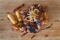 烤肋骨冠上了用烤肉汁和洋葱圈 免版税库存照片