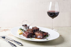 烤肋骨服务在有一杯的大白色板材红葡萄酒 库存照片