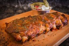 烤肋骨猪肉用烤肉汁和菜在木切板 库存图片