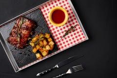 烤肋骨用被烘烤的土豆和辣椒调味汁 库存图片