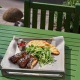 烤肋骨,服务在一个盘子,在芝麻和圆白菜沙拉素食主义者 街道食物Fron视图 库存图片