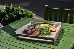 烤肋骨,服务在一个盘子,在芝麻和圆白菜沙拉素食主义者 街道食物Fron视图 库存照片