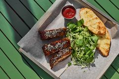 烤肋骨,服务在一个盘子,在芝麻和圆白菜沙拉素食主义者 街道食物Fron视图 免版税库存图片
