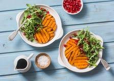 烤胡桃南瓜、芝麻菜和石榴沙拉在一张蓝色木桌上,顶视图 干净,有机,季节性,素食foo 免版税库存图片