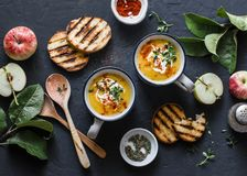 烤胡桃南瓜和苹果paleo饮食素食汤在黑暗的背景,顶视图 免版税库存图片