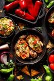 烤胡椒充塞用乳酪、烟肉、菜和草本,可口开胃菜的混合在黑背景的 免版税库存图片