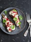 烤茄子用希脂乳、石榴、松果和香菜 可口开胃菜或快餐,在黑暗的背景 库存照片