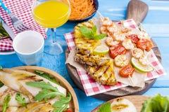 烤菜、虾、果子在一块木板材和香肠,汁液和沙拉在蓝色背景 面包正餐土豆夏天表蔬菜 空位 免版税图库摄影