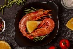 烤虾用柠檬和迷迭香在煎锅 免版税库存图片