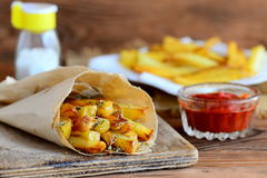 烤辣炸薯条在纸和在板材,在一个玻璃碗的西红柿酱,在一张木桌上的盐瓶 快的开胃菜 免版税库存照片