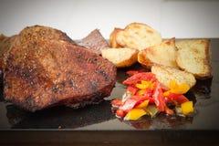 烤里脊肉牛排的多汁重水多的部分服务用烤土豆,并且在黑花岗岩的胡椒上 库存图片