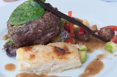烤里脊肉牛排的多汁重水多的部分服务用蕃茄和菜 免版税库存图片