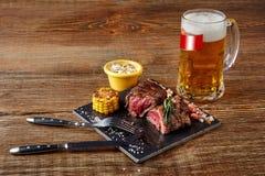 烤里脊肉牛排roastbeef和蘑菇酱油在黑切板和杯啤酒在木背景 免版税库存图片
