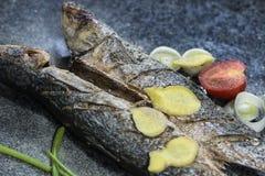 烤长凳竹刀鱼和被切的蕃茄在板岩背景 免版税库存图片