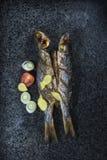 烤长凳竹刀鱼和被切的蕃茄在板岩背景 库存图片