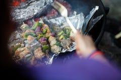 烤食物的成熟妇女在Firepit在森林 库存照片