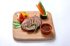 烤食物- BBQ牛排用辣调味汁和菜在一个木板 免版税库存照片