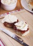 烤饼用草莓酱和打好的奶油 免版税库存图片