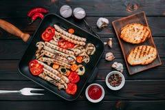 烤香肠和菜在一个格栅平底锅服务用调味汁 库存图片
