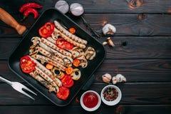 烤香肠和菜在一个格栅平底锅服务用调味汁 免版税图库摄影