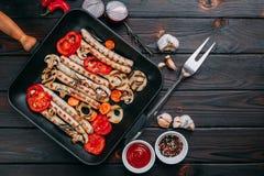 烤香肠和菜在一个格栅平底锅服务用调味汁 免版税库存图片