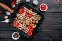 烤香肠和菜在一个格栅平底锅服务用调味汁 免版税库存照片