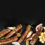 烤香肠有在BBQ板材的葱和大蒜顶视图 图库摄影