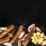 烤香肠有在BBQ板材的葱和大蒜顶视图 免版税库存图片