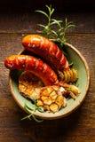 烤香肠用加法大蒜、葱和迷迭香在一张土气木桌上 免版税库存图片