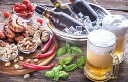 烤香肠用开胃菜和杯子啤酒 库存图片