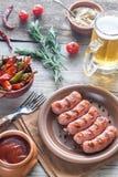 烤香肠用开胃菜和杯子啤酒 免版税库存照片