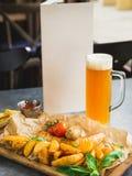 烤香肠用油煎的土豆和烂醉如泥的蕃茄在木板和杯啤酒 文本的纸牌 免版税库存照片