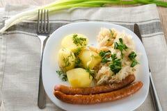 烤香肠用蒸的圆白菜德国泡菜和煮的土豆 免版税库存图片